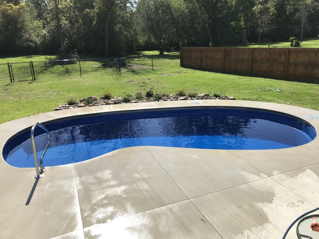 inground pool with concrete and railing