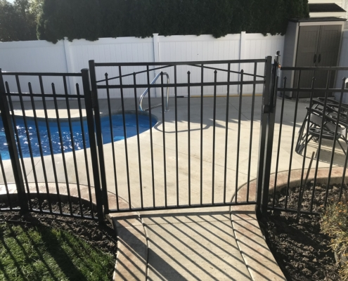 inground pool with concrete and fence